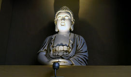 Ceramic decorative buda statue front view. A small buda made of ceramic used as a decoration in a vegetarian restaurant in mexico lighted from below royalty free stock photography