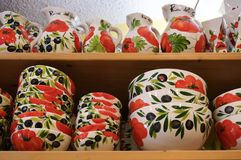 Ceramic dishes on the shelves in a store. Cute store selling colorful handmade tableware in traditional italian style Stock Photography