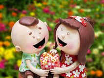 Ceramic doll boy and girl and gift on hands  flower garden backg Royalty Free Stock Photos