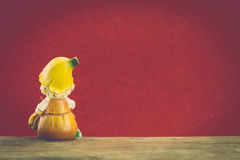 Ceramic doll sit on wood Royalty Free Stock Photography