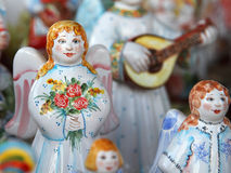 Ceramic dolls angels. Desk at the flea market: traditional russian handmade ceramic dolls men angels. One of them is with flowers Royalty Free Stock Photos