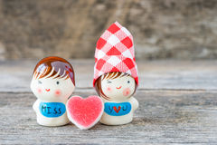Ceramic dolls sweetheart on wooden background. Stock Image