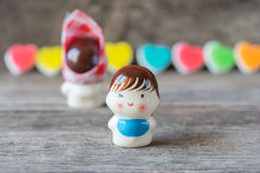 Ceramic dolls sweetheart on wooden background. Stock Photos