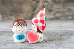 Ceramic dolls sweetheart on wooden background. Royalty Free Stock Image