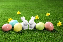 Ceramic Easter bunnies and dyed eggs. On green grass stock image