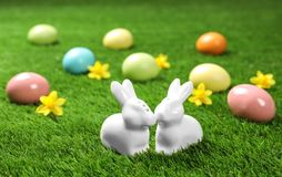 Ceramic Easter bunnies and dyed eggs. On green grass stock images