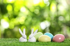 Ceramic Easter bunnies and dyed eggs on green grass against blurred background. Space for text stock image