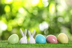 Ceramic Easter bunnies and dyed eggs on green grass against blurred background. Space for text royalty free stock images