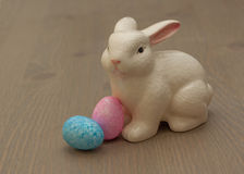 Ceramic Easter Bunny. White ceramic Easter bunny with two sparkly pastel eggs on a wood grained surface Royalty Free Stock Photo