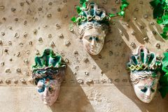 Ceramic feminine faces. Ceramic female faces on the wall of a house among flowers Stock Photography