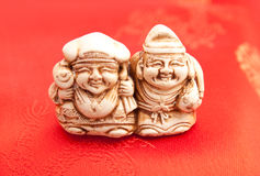 Ceramic figure chinese netsuke. Old eastern netsuke on red background Stock Photo