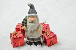 Santa Claus with four red Parcels on Snow Background, horizontal Royalty Free Stock Photos