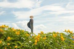 Ceramic figure in a yellow cassia bush stock image