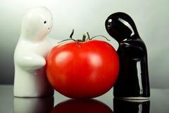 Ceramic figurines holding tomato. Black and white ceramic figurines holding red tomato Stock Images