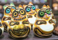 Ceramic figurines of smiling cats with large expressive eyes.  royalty free stock photography