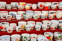 Ceramic flowerpots. Before red background, there are cartoon pictures of porcelain flower pots Stock Image