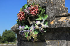 Ceramic flowers funeral wreath. Ceramic grave flowers at a thombstone in France royalty free stock photo
