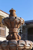 Ceramic Fountain. A ceramic fountain flowing with clear water down its levels in front of a Spanish style building in the background Stock Photo