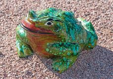 Ceramic frog in green and red colors sitting in the gravel stock photo
