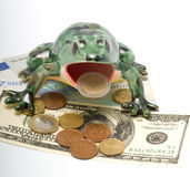 Ceramic frog and money. The ceramic frog sitting on money holds in a mouth a coin two euros Royalty Free Stock Image