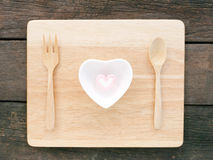 The ceramic heart shaped bowl and pink marshmallow and wooden spoon with fork on the wooden board. And old deep brown planks background for Valentine's day royalty free stock image