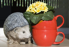 Ceramic hedgehog and red cups with flowers Royalty Free Stock Photo