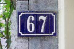 House number sixty seven 67. Ceramic house number sixty seven 67 Stock Photos