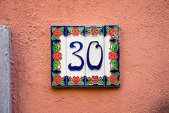 Ceramic house number 30. Ceramic house number thirty 30 on  plastered wall Stock Images