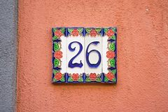 Ceramic house number 26. Ceramic house number twenty six 26 on a red plastered wall Stock Image