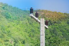 Ceramic insulation for electric cable hanging on the electric pylon with blue sky and green natural background. royalty free stock photo