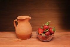 Ceramic jug and fresh strawberries royalty free stock images