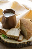 Ceramic jug with milk and a loaf rye black bread Stock Image