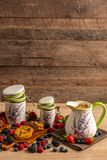 Ceramic jug and two size ceramic jars with cookies and mix of forest fruits on wooden background stock image