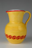 Ceramic jug in yellow and red. On neutral background Royalty Free Stock Photos