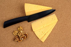 Ceramic knife with sliced cheese and walnuts Royalty Free Stock Photo