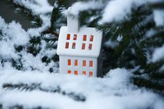Ceramic lantern house with burning candle on snow covered fir-tree branches in winter park. Ceramic toy lantern house with burning candle on snow covered fir Stock Photography