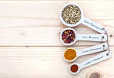 Ceramic measurement spoons filled with various spices on a pinewood  background Royalty Free Stock Photography