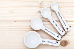 Ceramic measurement spoons on a pinewood background Royalty Free Stock Images
