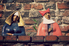 Ceramic Medieval Figures Sit on a Wall in Toruń, Poland Royalty Free Stock Photo