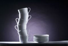 Ceramic movement in violet. A pile of cups in a s shape whit some dishes in a black and violet background, studio image composition Stock Image