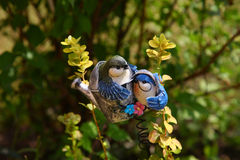 Ceramic ornament birds for the garden among plants in the sun Royalty Free Stock Photos