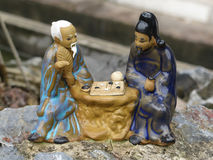 Ceramic ornament of two old asian men playing chess Stock Photos