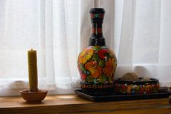Ceramic painted vase and pot and candle on windowsill. Traditional ukrainian handmade decoration. Ethnic rustic souvenirs. Culture and tradition concept royalty free stock photo