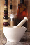 Pestle and mortar. Ceramic pestle and mortar on a kitchen work surface with oils in the background Stock Photos