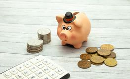 Ceramic piggy bank with coins on a wooden background, close-up stock photos