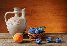 Ceramic pitcher, peaches and plums Stock Images