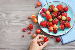 Ceramic plate with cherries, strawberries and raspberries at old wooden table. Royalty Free Stock Images