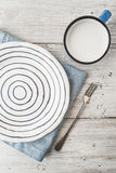 Ceramic plate with fork and cup of milk on the wooden table vertical Royalty Free Stock Photography