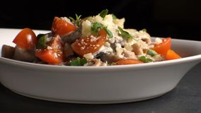 Ceramic plate with pasta, cheese, cherry and basil side view. Video. Horizontal stock video footage