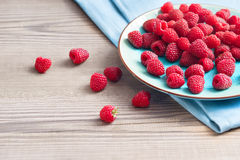 Ceramic plate with raspberries at old wooden table. Stock Photo